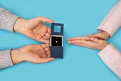 Équipez tenir la valentine bleue d'histoire d'amour de proposition d'ami d'amie de fond de mains de boîte d'anneaux de mariage Image stock
