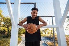 Équipez tenir le basket-ball, boule de rue, homme jouant, compétitions sportives, portrait extérieur, jeux de sport, homme de cou Photos libres de droits