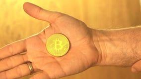 Équipez tenir le bitcoin d'or brillant dans sa main banque de vidéos