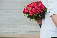 Équipez tenir le bouquet des roses rouges derrière le sien de retour surp d'ami Photo libre de droits