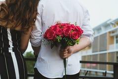 Équipez tenir le bouquet des roses rouges derrière le sien de retour surp d'ami Images libres de droits