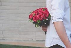 Équipez tenir le bouquet des roses rouges derrière le sien de retour surp d'ami Image stock