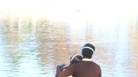 Équipez tenir le bras autour de la femme tandis qu'ils écoutant la musique par le lac banque de vidéos