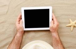 Équipez tenir le comprimé avec l'écran vide se trouvant sur la plage photo stock