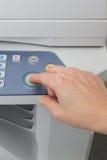 Équipez tenir le doigt sur un bouton marche d'imprimante à laser Image stock