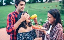 Équipez tenir le hot-dog dans le barbecue avec des amis photo libre de droits