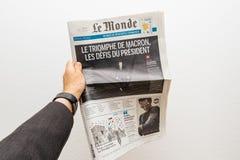 Équipez tenir le journal de Le Monde avec Emmanuel Macron sur le premier PAG Photographie stock