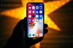 Équipez tenir le nouvel affichage 10 de l'iPhone X d'Apple avec l'étoile jaune Images stock