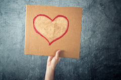Équipez tenir le papier de carton avec le dessin de forme de coeur Photographie stock