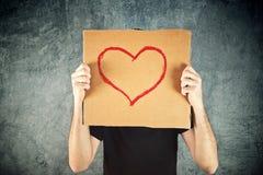 Équipez tenir le papier de carton avec le dessin de forme de coeur Photos libres de droits