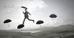 Équipez tenir le parapluie marchant à travers des parapluies au-dessus de paysage de nature photo stock