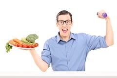 Équipez tenir le plat avec des légumes et une haltère Photos stock
