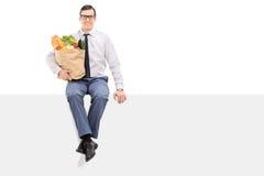 Équipez tenir le sac des épiceries posées sur le panneau Image libre de droits