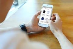 Équipez tenir le smartphone avec choisissent la chemise sur le site Web de commerce électronique photos stock
