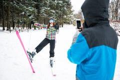 Équipez tenir le téléphone intelligent et prendre la photo de son amour avec l'eq de ski Photos stock