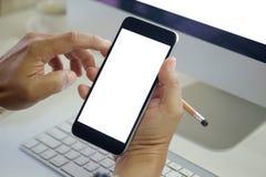 Équipez tenir le téléphone intelligent sur le bureau d'espace de travail de vue supérieure avec l'espace de copie Photos stock