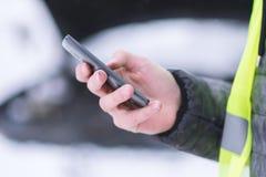 Équipez tenir le téléphone portable et appeler des services de voiture d'hiver pour aider image libre de droits