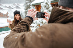 Équipez tenir le téléphone portable et prendre des photos de son amie Photographie stock