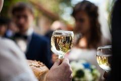 Équipez tenir le verre élégant de champagne dans un celebrati de restaurant Photo libre de droits