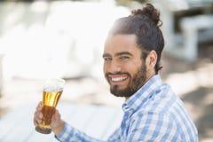 Équipez tenir le verre de bière en parc un jour ensoleillé Photographie stock libre de droits