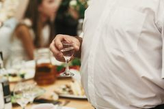 Équipez tenir le verre de vodka et le grillage à la réception de mariage pe Images stock