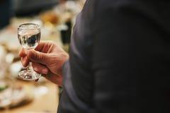 Équipez tenir le verre de vodka et le grillage à la réception de mariage pe Photos libres de droits