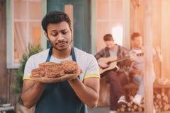 Équipez tenir les hamburgers sur le conseil en bois, amis avec la guitare se reposant derrière Photos stock