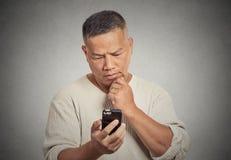Équipez tenir regarder son fond gris de mur d'isolement par téléphone intelligent photo stock