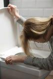 Équipez tenir ses cheveux du ` s d'amie tandis qu'elle vomit Photographie stock