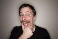 Équipez tenir son menton faisant un sourire très grand Image libre de droits