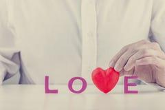 Équipez tenir un coeur rouge dans le mot - amour Images libres de droits