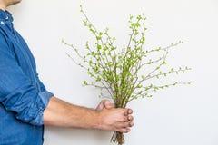 Équipez tenir un groupe de branches vertes de ressort Concept élégant lumineux de photo, d'eco et d'amour Photographie stock libre de droits