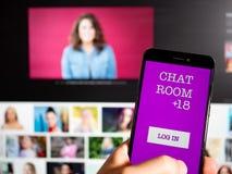 Équipez tenir un téléphone avec la causerie APP devant un écran photo libre de droits