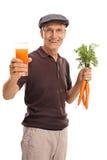 Équipez tenir un verre de jus et de carottes Photographie stock