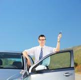 Équipez tenir une clé de voiture sur une route ouverte Photographie stock libre de droits