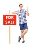 Équipez tenir une crème glacée par a à vendre le signe Photo stock