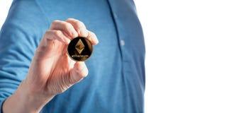 Équipez tenir une pièce de monnaie d'Ethereum d'éther sur un fond blanc image libre de droits