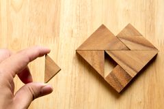 Équipez a tenu le morceau de puzzle de tangram pour accomplir le coeur Photo stock