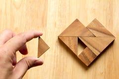 Équipez a tenu le morceau de puzzle de tangram pour accomplir la forme de coeur Photographie stock libre de droits