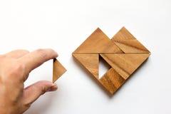 Équipez a tenu le morceau de puzzle de tangram pour accomplir la forme de coeur Photo libre de droits