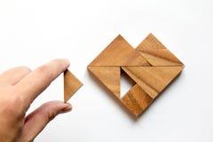 Équipez a tenu le morceau de puzzle de tangram pour accomplir la forme de coeur Photos stock