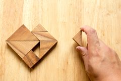 Équipez a tenu le morceau de puzzle de tangram pour accomplir la forme de coeur Photos libres de droits