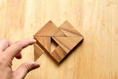 Équipez a tenu le morceau de puzzle de tangram pour accomplir la forme de coeur Photographie stock