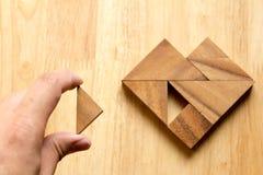 Équipez a tenu le morceau de puzzle de tangram pour accomplir la forme de coeur Image libre de droits