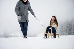 Équipez tirer la femme sur le traîneau dans la forêt d'hiver Photographie stock libre de droits