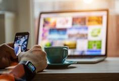 Équipez travailler au carnet, avec une tasse fraîche de café et de téléphone portable Image stock