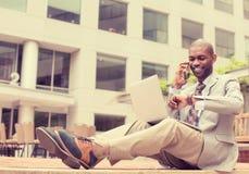 Équipez travailler sur l'ordinateur portable parlant au téléphone portable dehors Photo stock
