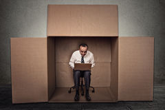 Équipez travailler sur l'ordinateur portable se reposant sur la chaise à l'intérieur de la boîte de carton Image libre de droits