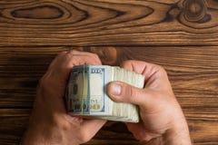 Équipez vérifier une pile épaisse de 100 billets d'un dollar Photo libre de droits