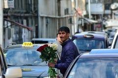 Équipez vendre des fleurs parmi des voitures à Bakou, capitale de l'Azerbaïdjan Photographie stock libre de droits